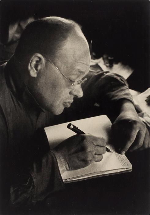 [Под влиянием Родченко] Фотография «И.Бабель записьменным столом»/ фото Г.Петрусова. [М., 1930].